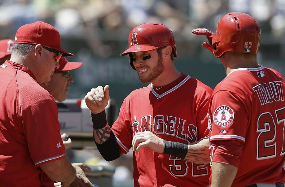 Los Angeles Angels'  Josh Hamilton, center, is congratulated by manager Mike Scioscia, left, and Mike Trout (27) after scoring on a single by J.B. Shuck against Oakland Athletics pitcher Tommy Milone during the fifth inning of a baseball game in Oakland, Calif., Wednesday, May 1, 2013. (AP Photo/Jeff Chiu) Photo: Jeff Chiu, Associated Press