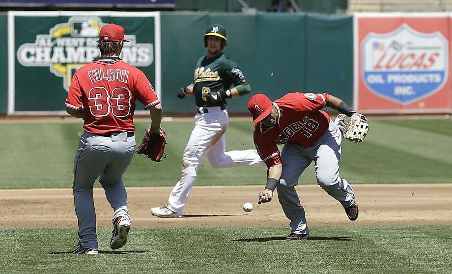 Los Angeles Angels third baseman Luis Jimenez (18) cannot handle a base hit by Oakland Athletics' Yoenis Cespedes during the first inning of a baseball game in Oakland, Calif., Wednesday, May 1, 2013.  Also pictured are Angels pitcher C.J. Wilson (33) and Athletics' Jed Lowrie. (AP Photo/Jeff Chiu) Photo: Jeff Chiu, Associated Press