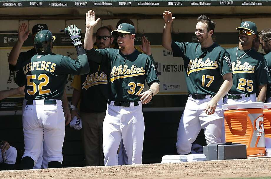 Oakland Athletics' Yoenis Cespedes (52) celebrates after scoring on Josh Donaldson's double off of Los Angeles Angels pitcher C.J. Wilson during the third inning of a baseball game in Oakland, Calif., Wednesday, May 1, 2013. (AP Photo/Jeff Chiu) Photo: Jeff Chiu, Associated Press
