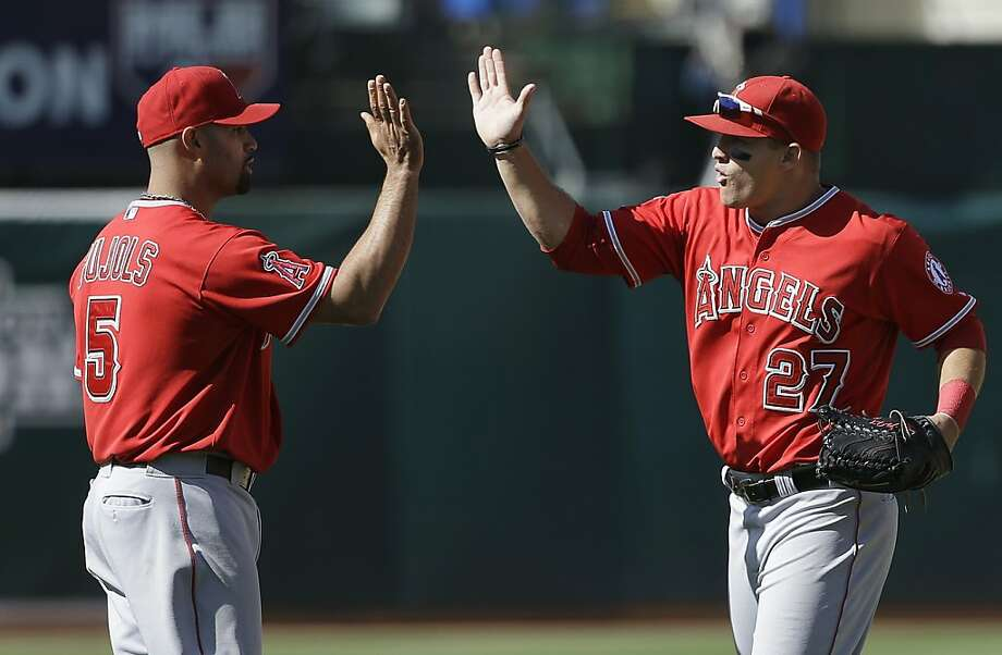 Los Angeles Angels first baseman Albert Pujols (5) and right fielder Josh Hamilton (32) celebrate after beating the Oakland Athletics in a baseball game in Oakland, Calif., Wednesday, May 1, 2013. The Angels won 5-4. (AP Photo/Jeff Chiu) Photo: Jeff Chiu, Associated Press