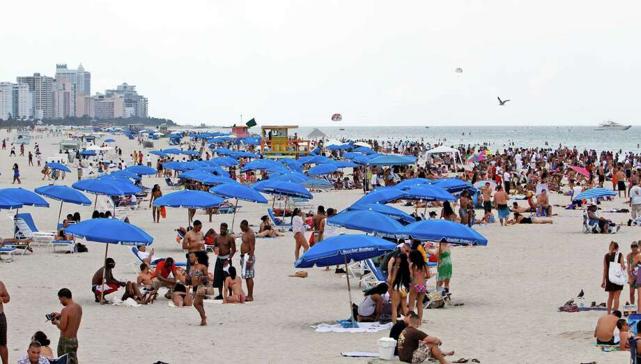In this Friday, May 28, 2010, file photo, tourists and local residents enjoy a day the the beach as Memorial Day weekend begins in the South Beach area of Miami, Beach, Fla. With a little advance planning, and some insider tips, summer vacations can be a lot less expensive. (AP Photo/Alan Diaz, File) Photo: Alan Diaz, Associated Press / AP