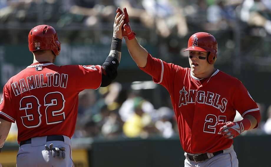 Los Angeles Angels' Mike Trout (27) celebrates after scoring on a sacrifice by Albert Pujols with Josh Hamilton (32) during the eighth inning of a baseball game against the Oakland Athletics in Oakland, Calif., Wednesday, May 1, 2013. (AP Photo/Jeff Chiu) Photo: Jeff Chiu, Associated Press