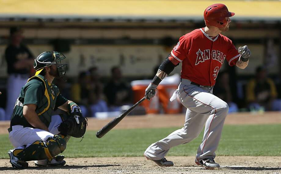 Los Angeles Angels' Josh Hamilton, right, singles in front of Oakland Athletics catcher Derek Norris during the eighth inning of a baseball game in Oakland, Calif., Wednesday, May 1, 2013. (AP Photo/Jeff Chiu) Photo: Jeff Chiu, Associated Press