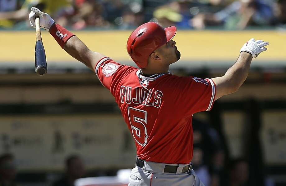 Los Angeles Angels' Albert Pujols (5) hits a sacrifice to score Mike Trout during the eighth inning of a baseball game against the Oakland Athletics in Oakland, Calif., Wednesday, May 1, 2013. (AP Photo/Jeff Chiu) Photo: Jeff Chiu, Associated Press
