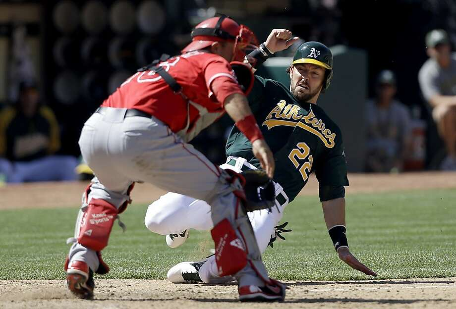 Oakland Athletics' Luke Montz scores against Los Angeles Angels catcher Hank Conger during the eighth inning of a baseball game in Oakland, Calif., Wednesday, May 1, 2013. The Angels won 5-4. (AP Photo/Jeff Chiu) Photo: Jeff Chiu, Associated Press