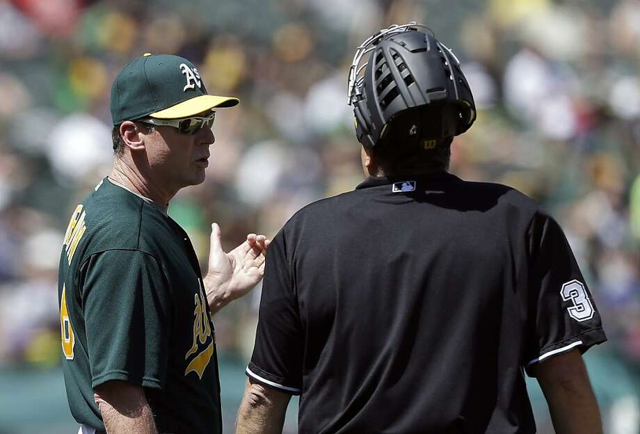 Oakland Athletics manager Bob Melvin, left, talks with umpire Gary Cederstrom (38) after a ball hit by Los Angeles Angels' Mark Trumbo was reviewed and ruled a home run during the sixth inning of a baseball game in Oakland, Calif., Wednesday, May 1, 2013. (AP Photo/Jeff Chiu) Photo: Jeff Chiu, Associated Press