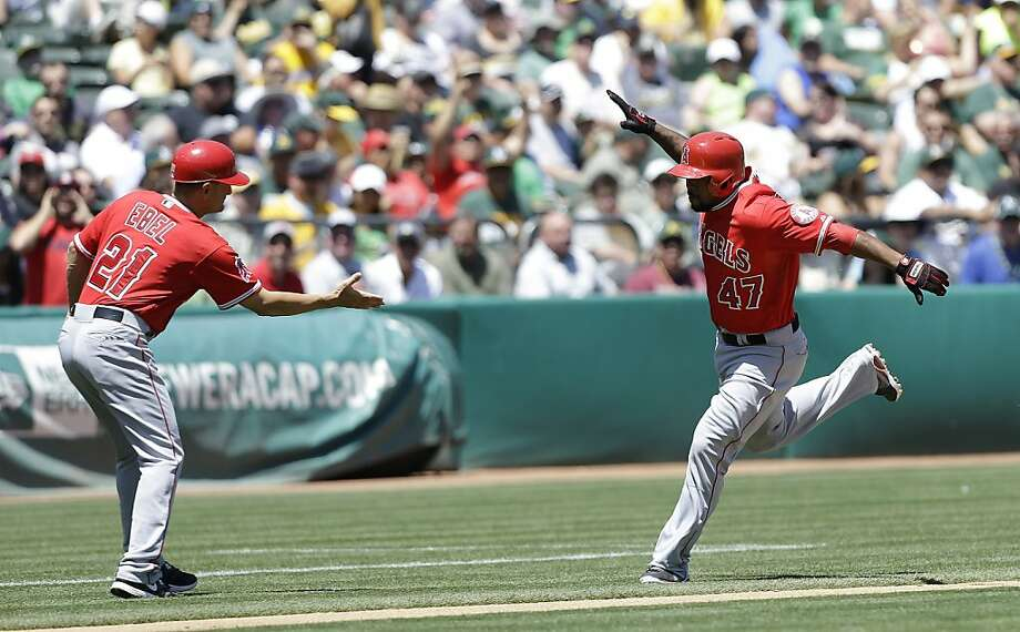 Los Angeles Angels' Howie Kendrick (47) celebrates with third base coach Dino Ebel (21) after hitting a solo home run off of Oakland Athletics pitcher Tommy Milone during the second inning of a baseball game in Oakland, Calif., Wednesday, May 1, 2013. (AP Photo/Jeff Chiu) Photo: Jeff Chiu, Associated Press
