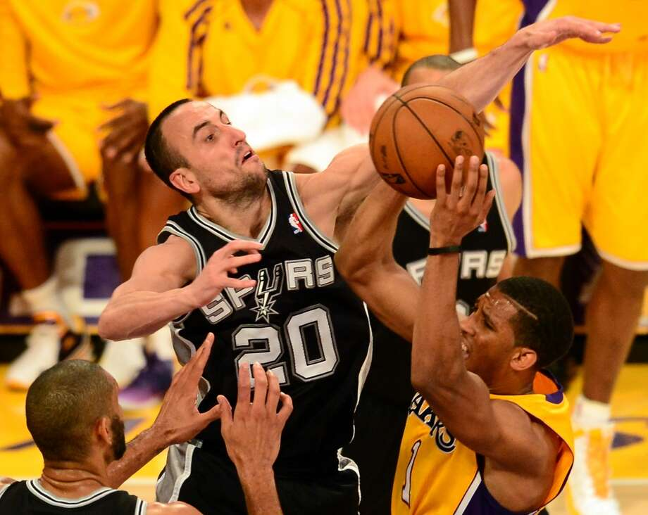 Darius Morris (R) of the Los Angeles Lakers attempts to navigate under pressure from Manu Ginobili (C) and Tim Duncan (L) of the San Antonio Spurs during Game Three of the NBA Western Conference Quarterfinal Playoffs at Staples Center in Los Angeles, California on April 26, 2013.