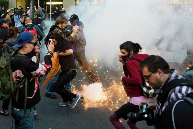 "Protesters react to a ""blast ball"" thrown by police officers in downtown Seattle. Photo: JORDAN STEAD, SEATTLEPI.COM / SEATTLEPI.COM"