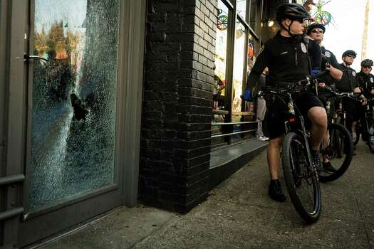 Police watch over a local business that suffered window damage. Photo: JORDAN STEAD, SEATTLEPI.COM / SEATTLEPI.COM