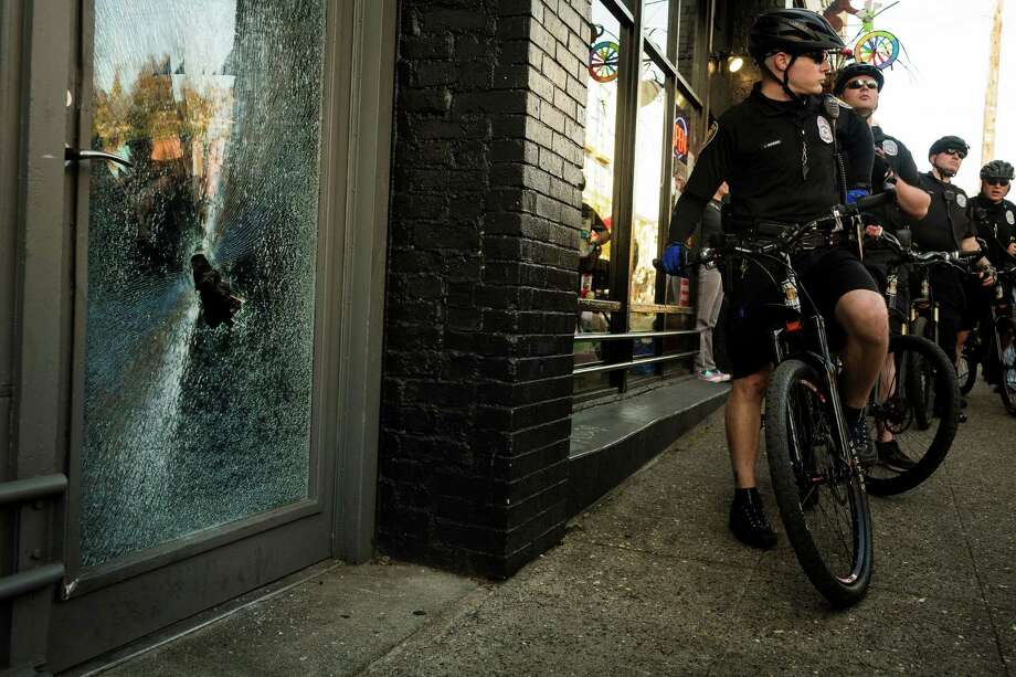 Police watch over a local business that suffered window damage via a violent protester during the May Day riots Wednesday, May 1, 2013, in Seattle. By late evening, police reported that 18 persons had been arrested for assault and property damage. Eight police officers were hurt. Photo: JORDAN STEAD, SEATTLEPI.COM / SEATTLEPI.COM