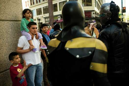 Passerbys watch local superhero Phoenix Jones, center, and other costumed crime fighters. Photo: JORDAN STEAD, SEATTLEPI.COM / SEATTLEPI.COM