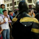 Passerbys watch local superhero Phoenix Jones, center, and other costumed crime fighters.