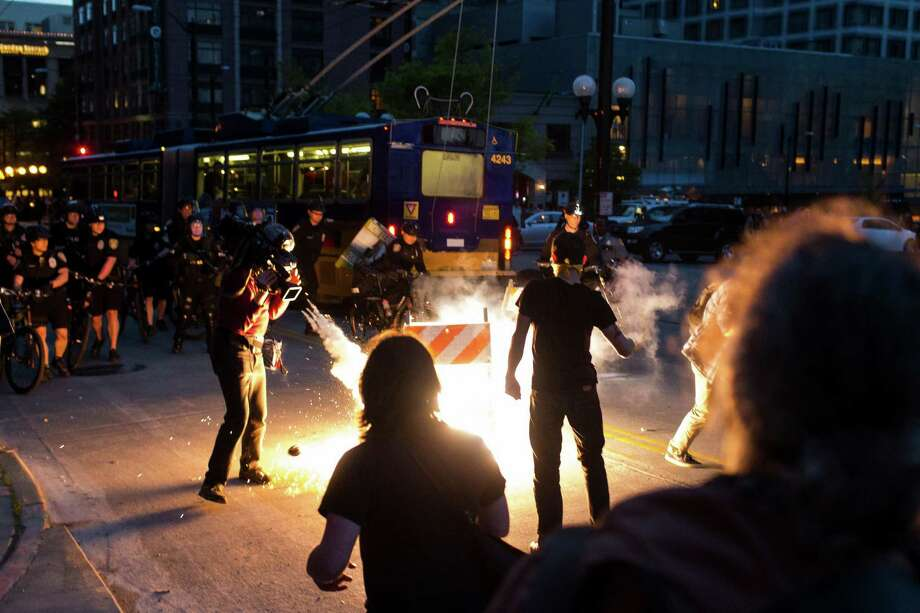 "Protesters scatter as a ""blast ball"" thrown by police officers detonates. Photo: JORDAN STEAD, SEATTLEPI.COM / SEATTLEPI.COM"