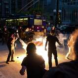 """Protesters scatter as a """"blast ball"""" thrown by police officers detonates."""