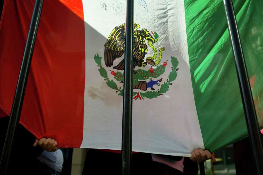 A pair of hands pull down a Mexican flag to conceal the occupants of a mock jail on a float. Photo: JORDAN STEAD, SEATTLEPI.COM / SEATTLEPI.COM