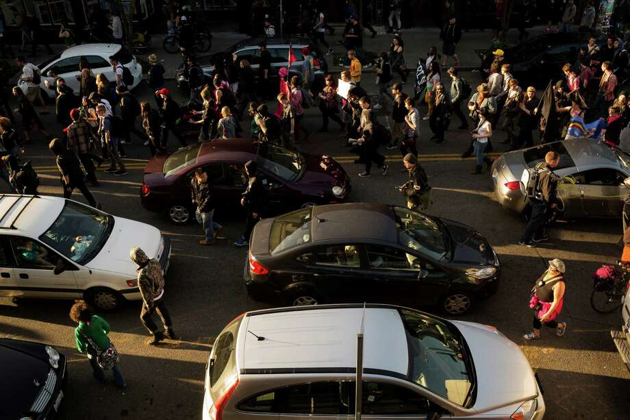 Protesters stop traffic with a swarm of bodies during the May Day march. Photo: JORDAN STEAD, SEATTLEPI.COM / SEATTLEPI.COM