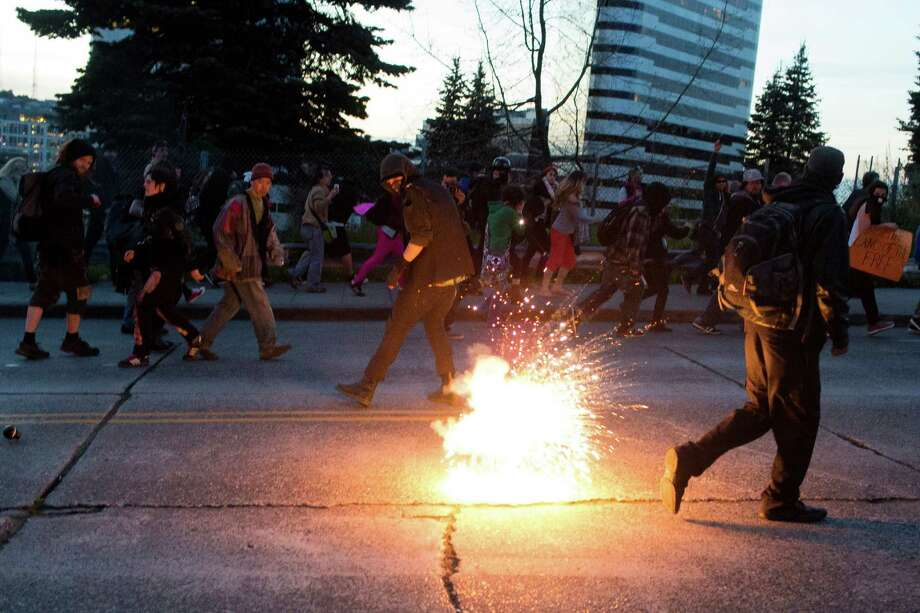 Protesters scatter as a police-deployed flash bang explodes in the street during the May Day riots Wednesday, May 1, 2013, in Seattle. By late evening, police reported that 18 persons had been arrested for assault and property damage. Eight police officers were hurt. Photo: JORDAN STEAD, SEATTLEPI.COM / SEATTLEPI.COM