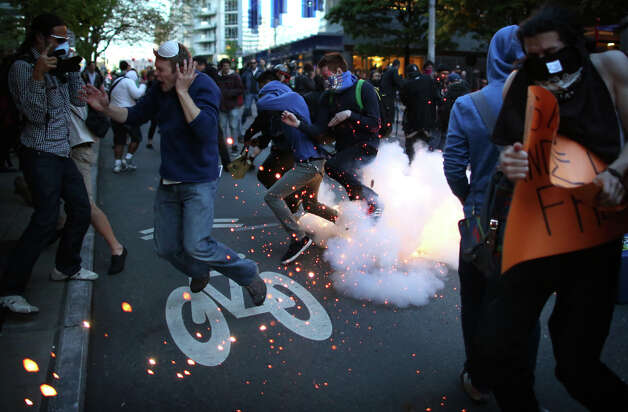 "Protesters and members of the media react to a ""blast ball"" thrown by police officers during a May Day march in downtown Seattle on Wednesday, May 1, 2013. Police aggressively responded to marchers as they blocked t"