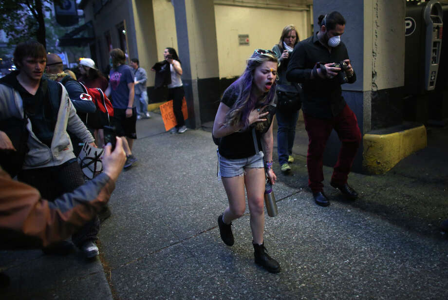 A woman chokes from pepper spray during a May Day march in downtown Seattle on Wednesday, May 1, 2013. Police aggressively responded to marchers as they blocked traffic and some threw objects at officers. Police responded with pepper spray and blast balls, firework-like devices that emit OC spray. Photo: JOSHUA TRUJILLO, SEATTLEPI.COM / SEATTLEPI.COM