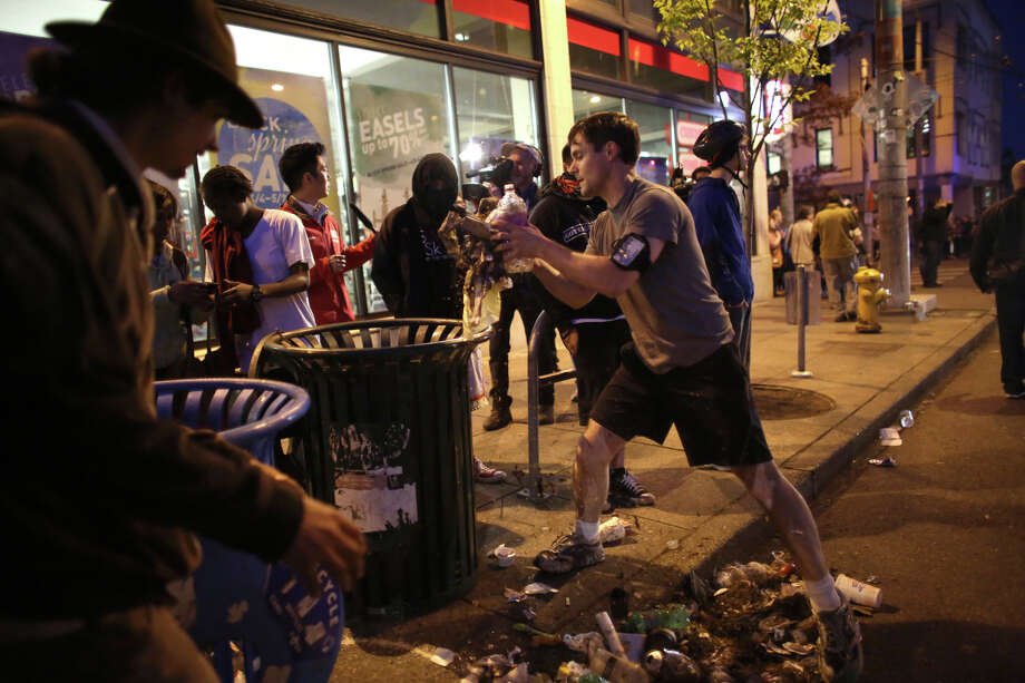 A man cleans up trash thrown by protesters during a May Day march in Capitol Hill on Wednesday, May 1, 2013. Police aggressively responded to marchers as they blocked traffic and some threw objects at officers. Police responded with pepper spray and blast balls, firework-like devices that emit OC spray. Photo: JOSHUA TRUJILLO, SEATTLEPI.COM / SEATTLEPI.COM