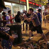 A man cleans up trash thrown by protesters as they overturned trash cans on Broadway in Capitol Hill.