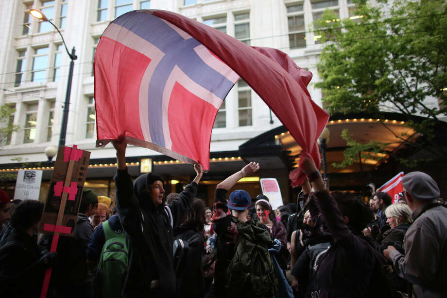 Participants dance with a flag during a May Day march in downtown Seattle. Police aggressively responded to marchers as they blocked traffic and some threw objects at officers and broke windows.  Photo: JOSHUA TRUJILLO, SEATTLEPI.COM / SEATTLEPI.COM