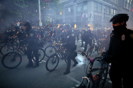 Police officers advance through a cloud of smoke during a May Day march in downtown Seattle. Photo: JOSHUA TRUJILLO, SEATTLEPI.COM / SEATTLEPI.COM