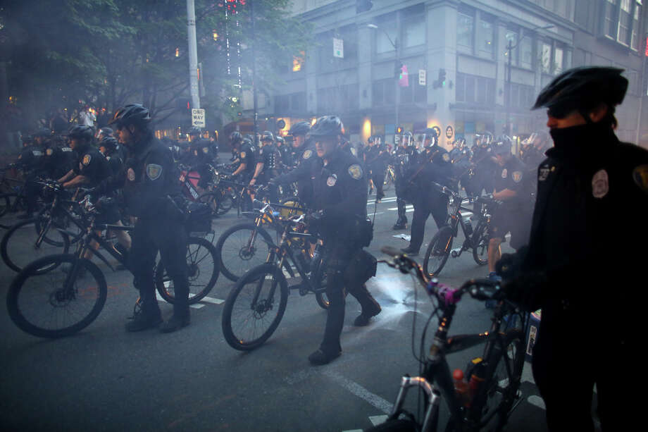 Police officers advance through a cloud of smoke during a May Day march in downtown Seattle on Wednesday, May 1, 2013. Police aggressively responded to marchers as they blocked traffic and some threw objects at officers. Police responded with pepper spray and blast balls, firework-like devices that emit OC spray. Photo: JOSHUA TRUJILLO, SEATTLEPI.COM / SEATTLEPI.COM
