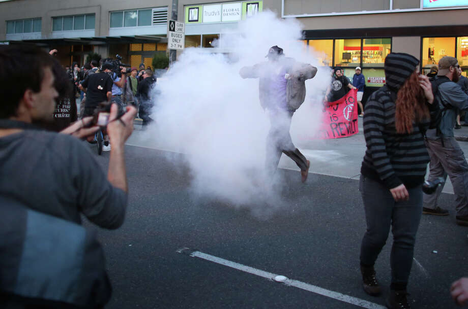 "Smoke from a ""blast ball"" envelopes a man near Westlake Mall. Photo: JOSHUA TRUJILLO, SEATTLEPI.COM / SEATTLEPI.COM"