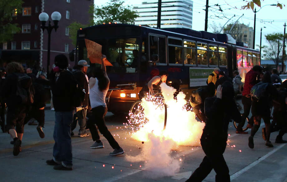 A blast ball explodes during a May Day march in downtown Seattle on Wednesday, May 1, 2013. Police aggressively responded to marchers as they blocked traffic and some threw objects at officers. Police responded with pepper spray and blast balls, firework-like devices that emit OC spray. Photo: JOSHUA TRUJILLO, SEATTLEPI.COM / SEATTLEPI.COM