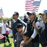 From left, Javier Valencia, his son Anthony, Indira Valencia, her son Cesar and friend Maria Orozco hold flags during an immigrant rights May Day rally.