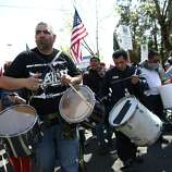 Participants play drums during an immigrant rights May Day rally.