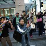 Spectators take photos during an immigrant rights May Day rally and march.