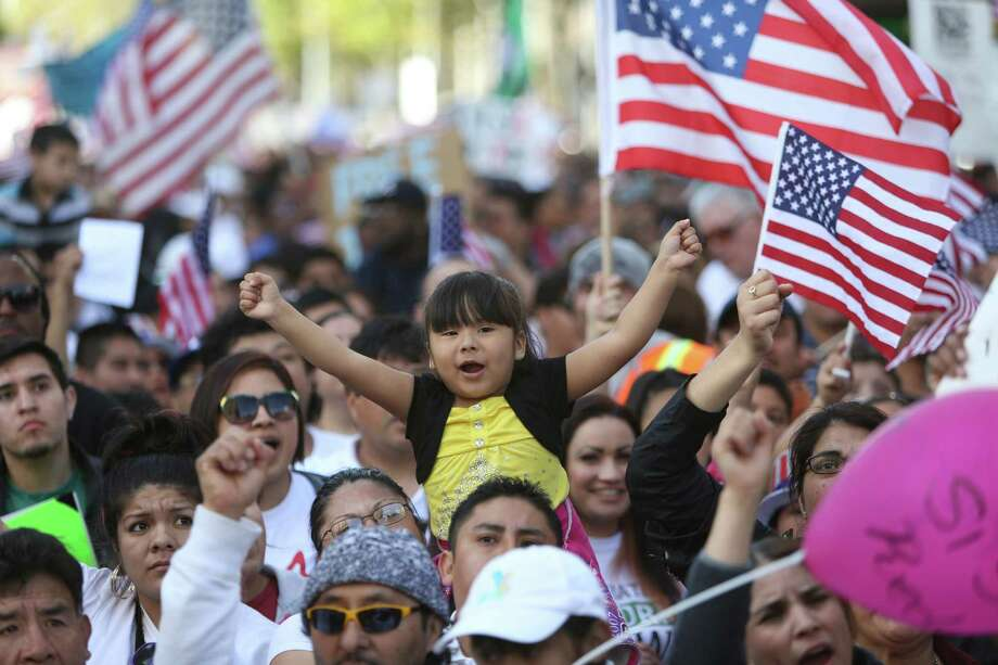 A young participant throws up her arms during an immigrant rights May Day rally in Seattle on Wednesday, May 1, 2013. Thousands of people marched, demanding immigration reform. A handful of black-clad protesters participated but the march was peaceful. Photo: JOSHUA TRUJILLO, SEATTLEPI.COM / SEATTLEPI.COM
