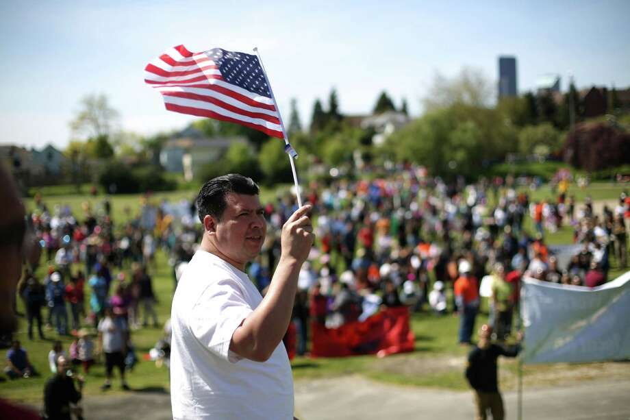 A marcher holds up a flag during an immigrant rights May Day rally at Judkins Park. Photo: JOSHUA TRUJILLO, SEATTLEPI.COM / SEATTLEPI.COM