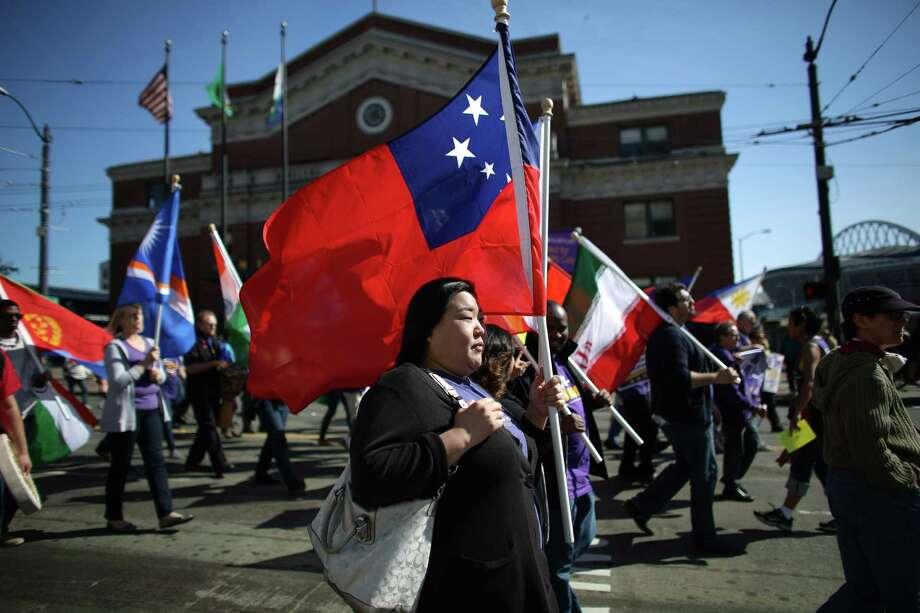 People march with flags during an immigrant rights May Day rally. Thousands of people marched, demanding immigration reform. The march was