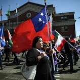 People march with flags during an immigrant rights May Day rally. Thousands of people marched, demanding immigration reform. The march was  peaceful and was unrelated to a later march that ended with police  using bang balls and pepper spray to disperse the crowd. The later march resulted in 17 arrests and injuries to officers.