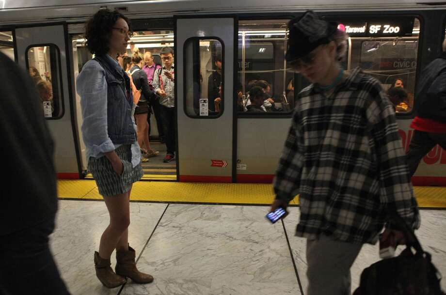 Jordan Epstein (left), from San Francisco, waits for her train in the Civic Center Metro station in San Francisco, California,  on Tuesday, April 30, 2013.  She always listens for platform announcements while waiting for her train.