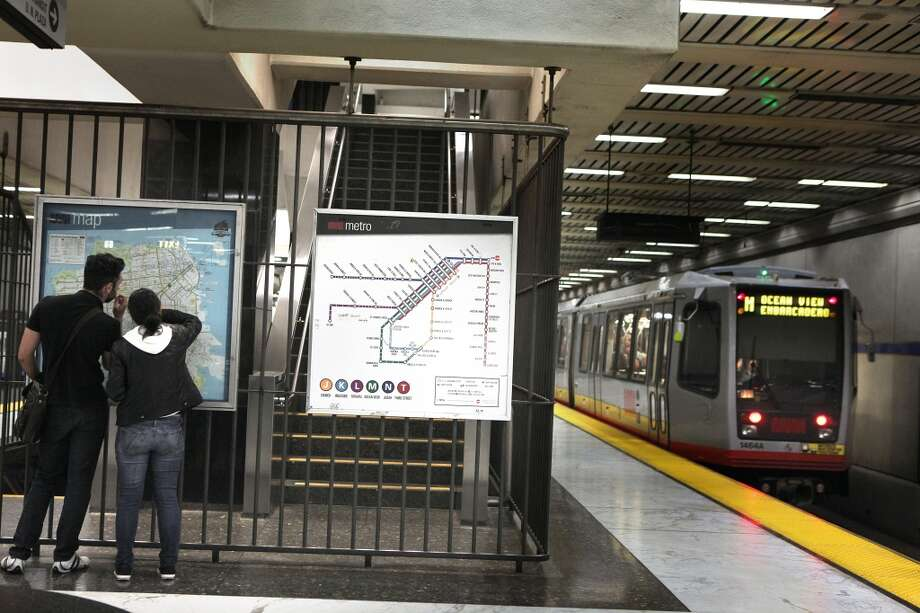 Passengers check the route map at the Civic Center Metro station in San Francisco, California, as they hear automated announcements overhead on Tuesday, April 30, 2013.