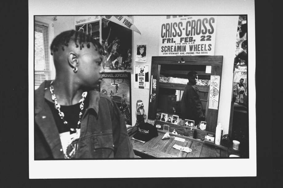 Mack Daddy (Chris Kelly), member of rap duo Kris Kross, admiring himself in dressing table mirror which has poster above it of the duo's first mall performance then called Criss-Cross in his bedroom at home.  (Photo by Acey Harper//Time Life Pictures/Getty Images)