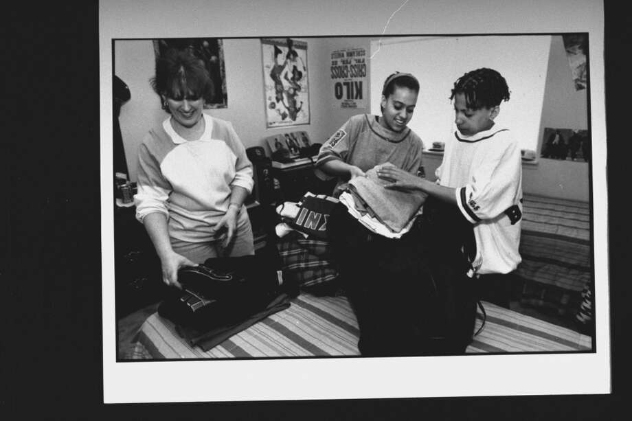 1992- Daddy Mack (Chris Smith) (R), a member of rap duo Kris Kross, being helped w. packing his clothes into duffel bag by his sister Jennifer (C), 16, & mom Angela, as he packs for his European tour at home.  (Photo by Acey Harper//Time Life Pictures/Getty Images)