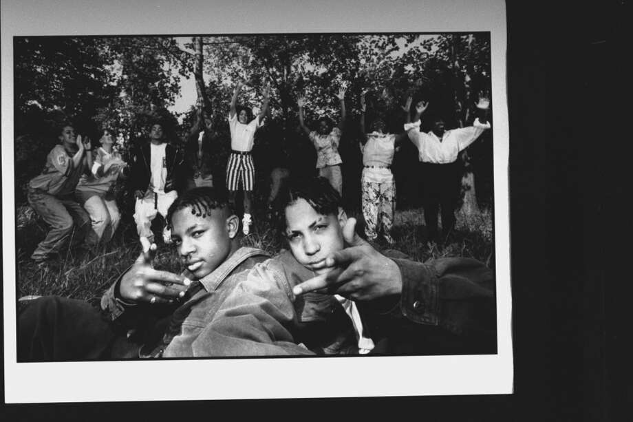 1992 - (L-R) Kris Kross rap duo Mack Daddy (Chris Kelly) & Daddy Mack (Chris Smith) sit in grass while 9 members of their families jump for joy behind them over the success of their 1st single Jump.  (Photo by Acey Harper//Time Life Pictures/Getty Images)