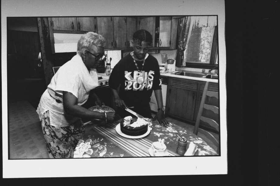Mack Daddy (Chris Kelly), member of rap duo Kris Kross, spreading icing on freshly baked carrot cake as he his grandma Rosina Williams holds the bowl in kitchen at home.  (Photo by Acey Harper//Time Life Pictures/Getty Images)