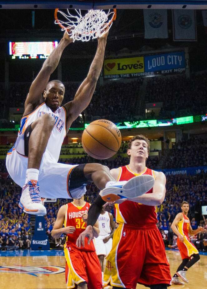Thunder power forward Serge Ibaka dunks past Rockets center Omer Asik.