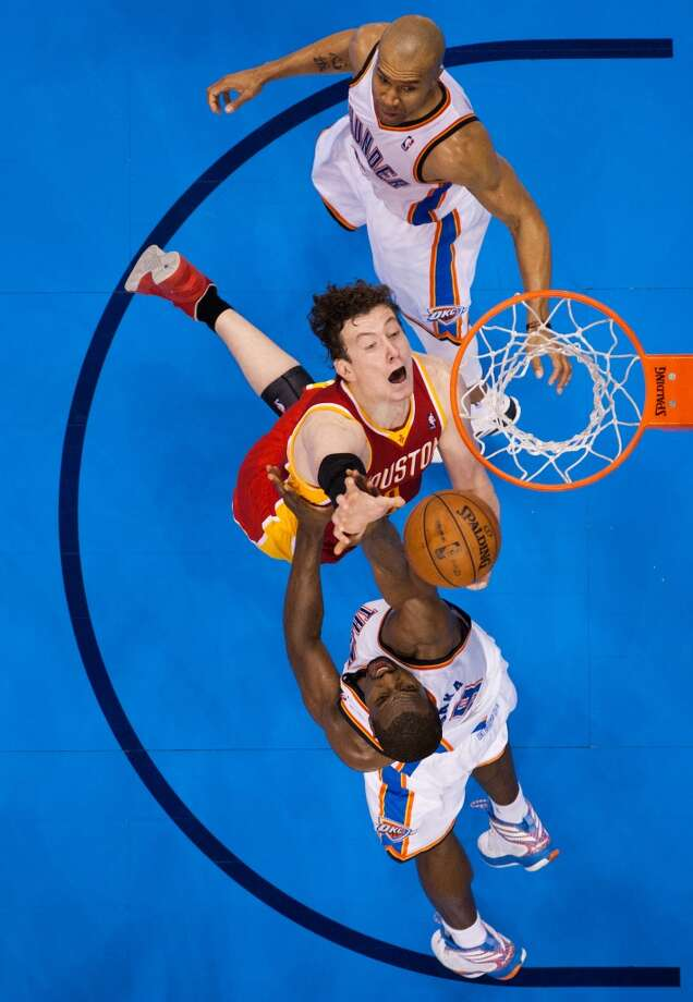 Rockets center Omer Asik is fouled by Thunder power forward Serge Ibaka.