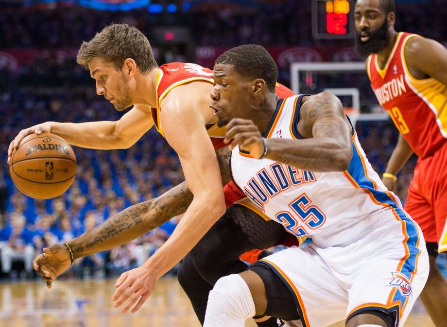 Thunder guard DeAndre Liggins reaches in to try and steal the ball from Rockets forward Chandler Parsons.