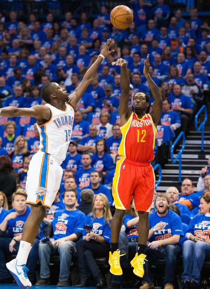 Rockets point guard Patrick Beverley shots over Thunder point guard Reggie Jackson.