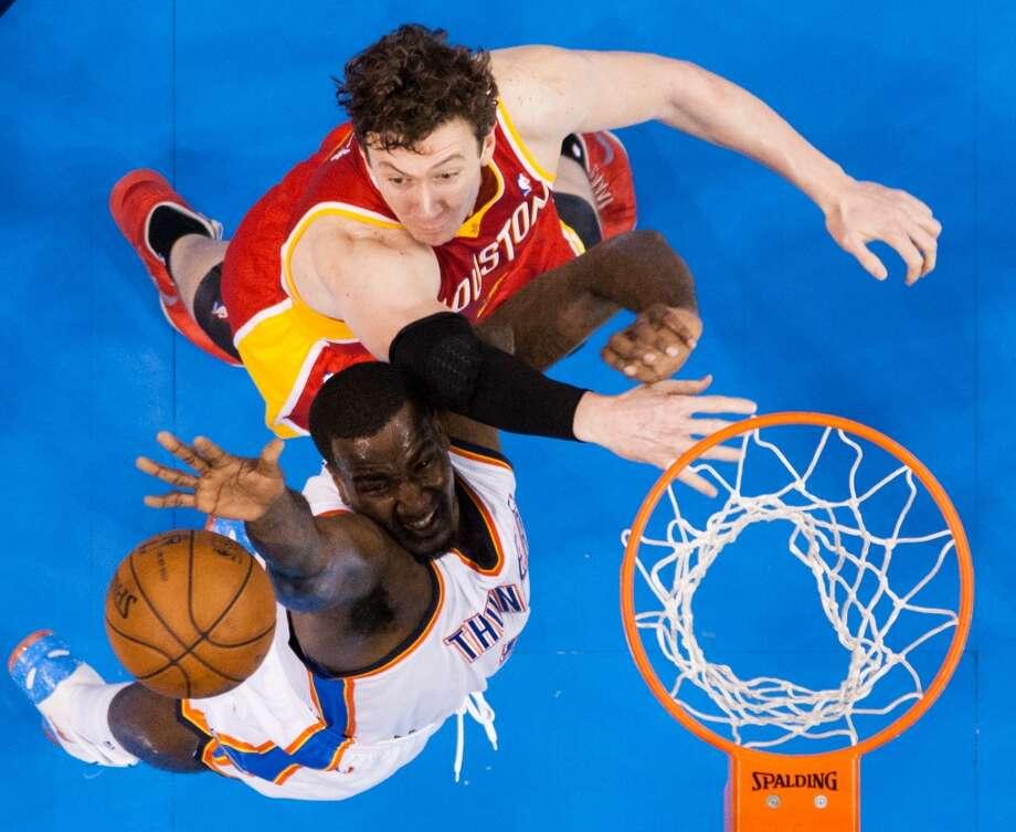 Rockets center Omer Asik fights for a rebound against Thunder center Kendrick Perkins.