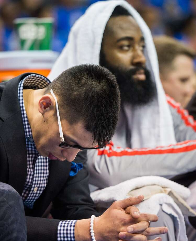 Rockets point guard Jeremy Lin and shooting guard James Harden watch from the bench.